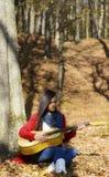 美丽的妇女吉他演奏员女孩在森林里 免版税库存照片