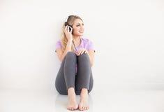 年轻美丽的妇女听与耳机的音乐 免版税库存图片