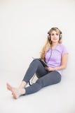年轻美丽的妇女听与耳机的音乐 图库摄影