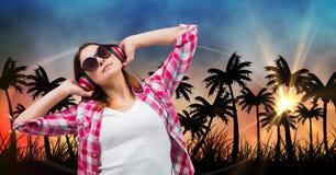 美丽的妇女听的音乐通过耳机,当站立反对剪影树时 图库摄影