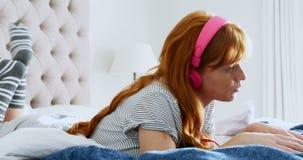 美丽的妇女听的音乐,当使用膝上型计算机4k时 股票视频