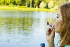 美丽的妇女吹的泡影在湖附近的夏天 库存照片