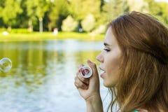 美丽的妇女吹的泡影在湖附近的夏天 库存图片