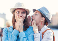 年轻美丽的妇女告诉秘密对她的朋友在城市 免版税库存图片