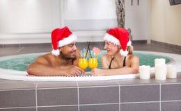 美丽的妇女和人有放松在极可意浴缸的圣诞老人帽子的在sp 库存照片