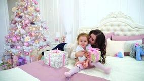 美丽的妇女和小女孩、母亲和女儿使用的好心情的互相在明亮的卧室在床上近 股票录像