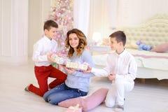 美丽的妇女和有同情心的母亲有两名男孩exchang的 免版税图库摄影