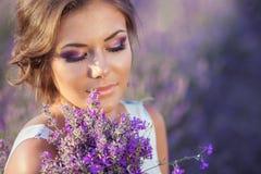 美丽的妇女和淡紫色领域 免版税库存图片