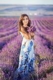 美丽的妇女和淡紫色领域 免版税库存照片