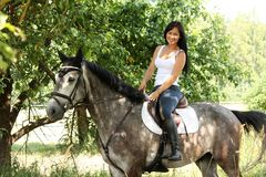 美丽的妇女和灰色马画象在庭院里 免版税库存照片