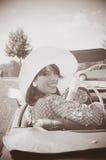 美丽的妇女和老汽车,五十年代样式 免版税图库摄影