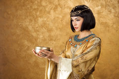 美丽的妇女喜欢有杯子的埃及女王帕特拉在金黄背景 免版税库存照片