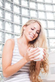 年轻美丽的妇女喝咖啡。 库存图片