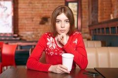 美丽的妇女喝在咖啡馆的茶。 库存照片