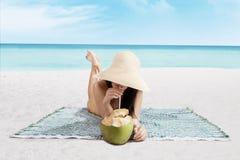 美丽的妇女喝椰子水 免版税库存图片