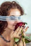 美丽的妇女嗅到红色玫瑰 免版税库存照片