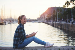 年轻美丽的妇女固定的单元电话和微笑对她在海港附近等待的她的朋友, 免版税库存照片