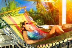 美丽的妇女在一个吊床放松在一座热带平房 库存图片