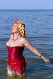 美丽的妇女在一个红色束腰和花卉花冠 免版税库存图片