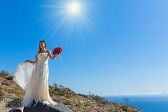 美丽的妇女在一块高石头站立 库存图片