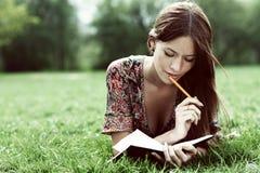 年轻美丽的妇女在一棵草放置在有一本日志的公园在ha 图库摄影