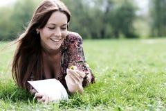 年轻美丽的妇女在一棵草放置在有一本日志的公园在ha 库存照片