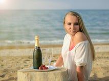 美丽的妇女在与一个瓶的明媚的阳光下香槟和草莓在海滩 库存照片