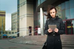 美丽的妇女在使用电子片剂的镇 免版税库存图片