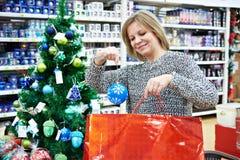 美丽的妇女在假日红色袋子上把一个蓝色圣诞节球放 库存图片