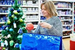 美丽的妇女在假日蓝色袋子上把红色圣诞节球放 库存照片