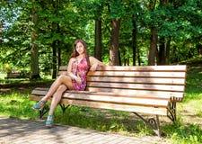 美丽的妇女在公园休息坐一条长凳 免版税库存照片