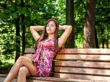 美丽的妇女在公园休息坐一条长凳 图库摄影