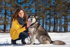 美丽的妇女在冬天积雪的木头走 免版税库存图片
