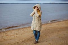 美丽的妇女在冬天给支持河和看穿衣对冬天日落 季节性,时尚和关系 库存图片