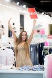 美丽的妇女在商店满意对折扣 免版税库存照片