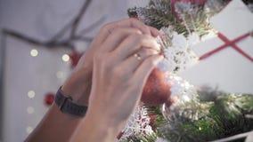 美丽的妇女在圣诞树附近站立并且装饰她与玩具 影视素材