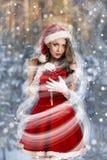美丽的妇女在圣诞老人礼服 图库摄影