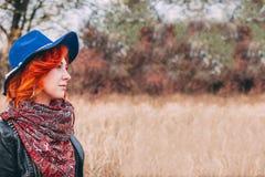 美丽的妇女在多云天气的公园走秋天 免版税库存照片