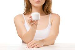 美丽的妇女在她的手上坐一个瓶子奶油 免版税库存图片