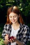 年轻美丽的妇女在她的手上的拿着一棵樱桃在庭院里 图库摄影