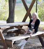 美丽的妇女在度假在湖的,秋天 免版税库存图片