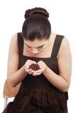 美丽的妇女在手上的坐和拿着咖啡豆。 免版税库存照片