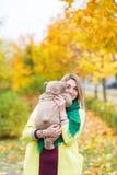 美丽的妇女在拿着玩具熊的秋天公园 图库摄影