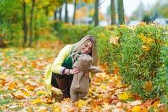 美丽的妇女在拿着玩具熊的秋天公园 免版税库存照片