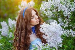 美丽的妇女在春天以猫的形式庭院丁香 免版税库存照片