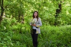 年轻美丽的妇女在有春黄菊花束的森林里站立  免版税图库摄影