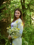 年轻美丽的妇女在有春黄菊花束的森林里站立  免版税库存图片
