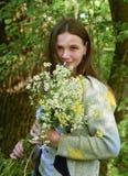 年轻美丽的妇女在有春黄菊花束的森林里站立  库存照片