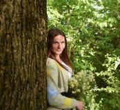 年轻美丽的妇女在有春黄菊花束的森林里站立  免版税库存照片