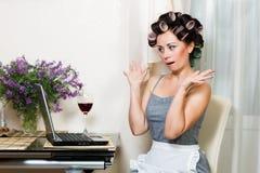 美丽的妇女在有笔记本的厨房里 免版税库存照片